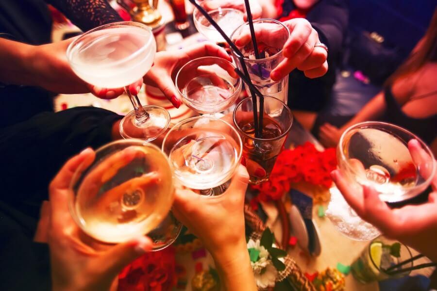 Grupa znajomych wznosi toast kieliszkami i szklankami z alkoholem.