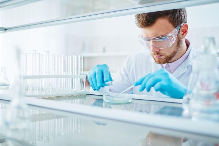 Laborant w okularach ochronnych i rękawiczkach, wykonuje swoją pracę.