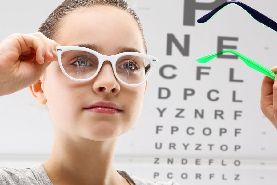 Dziewczynka podczas badania wzroku i przymiarki okularów korekcyjnych.