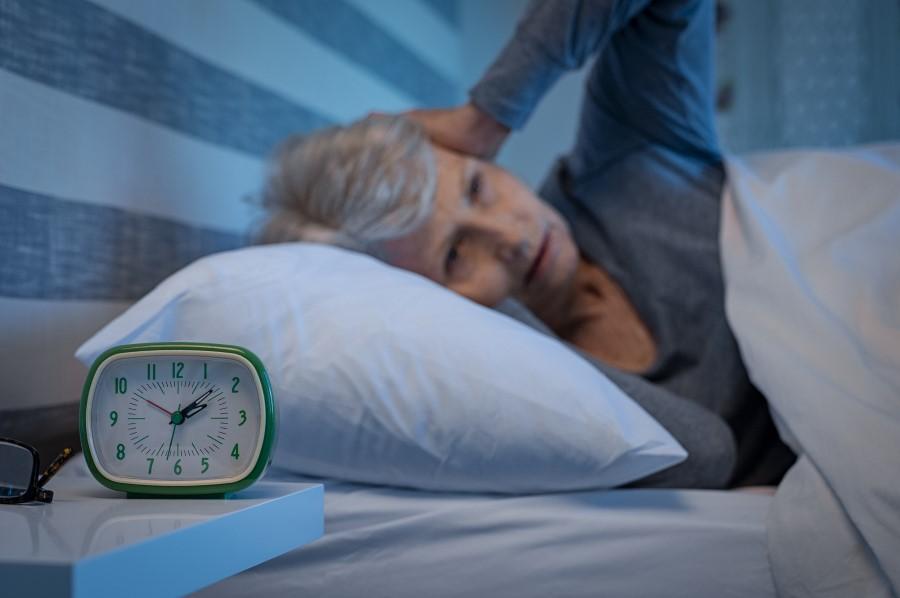Starsza kobieta leży w łóżku, cierpi na bezsenność. Zegarek pokazuje godzinę 2 w nocy.