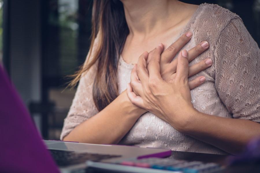 Kobieta chwyta się za klatkę piersiową, odczuwa ból piersi.