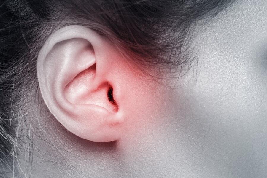 Czarno-białe zdjęcie, zbliżenie na bolące, zaczerwienione ucho.