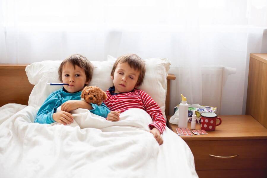 Mali chłopcy leżą w łóżku z gorączką, przechodzą chorobę bostońską.