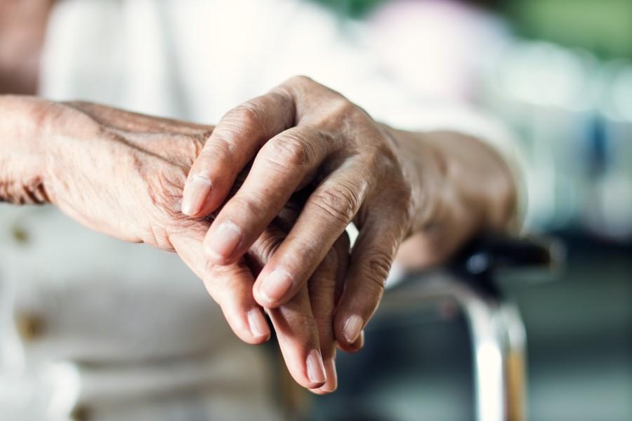 Dłonie starszej kobiety chorującej na chorobę Parkinsona.
