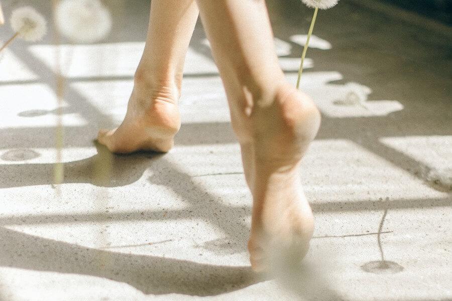 Zbliżenie na kobiece, bose stopy idące po betonowej posadzce.