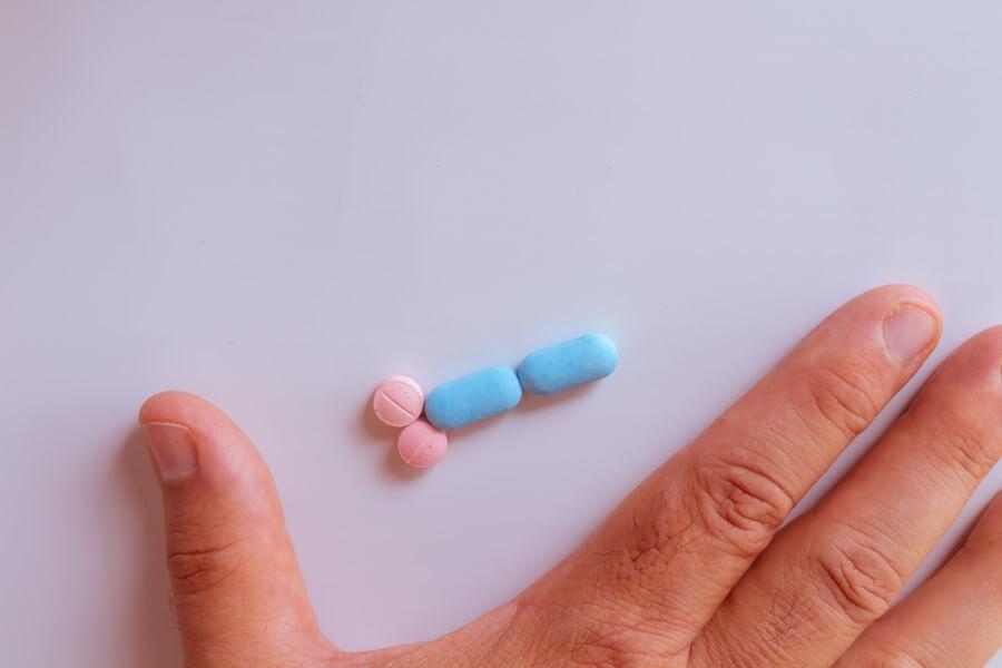 Męska dłoń, obok różowe i niebieskie tabletki.