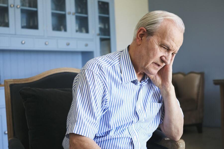 Starszy, zmartwiony mężczyzna siedzi na fotelu. Zmaga się z postępującą demencją starczą.