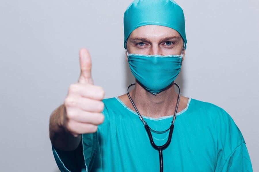 Lekarz w fartuchu, czepku i maseczce. Ma na szyi stetoskop.