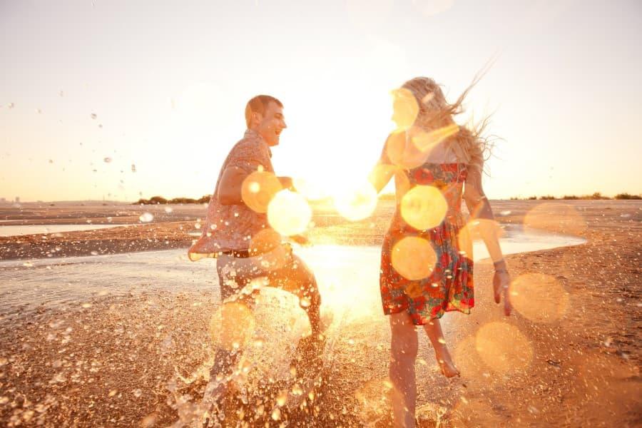 Para młodych ludzi bawi się nad brzegiem morza.