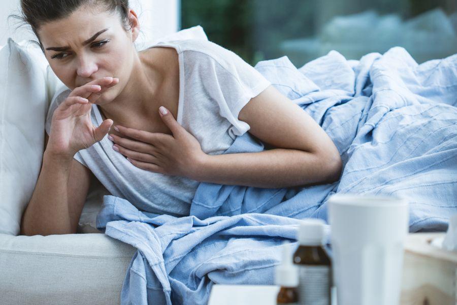 Młoda kobieta leży w łóżku, źle się czuje z powodu gorączki reumatycznej.