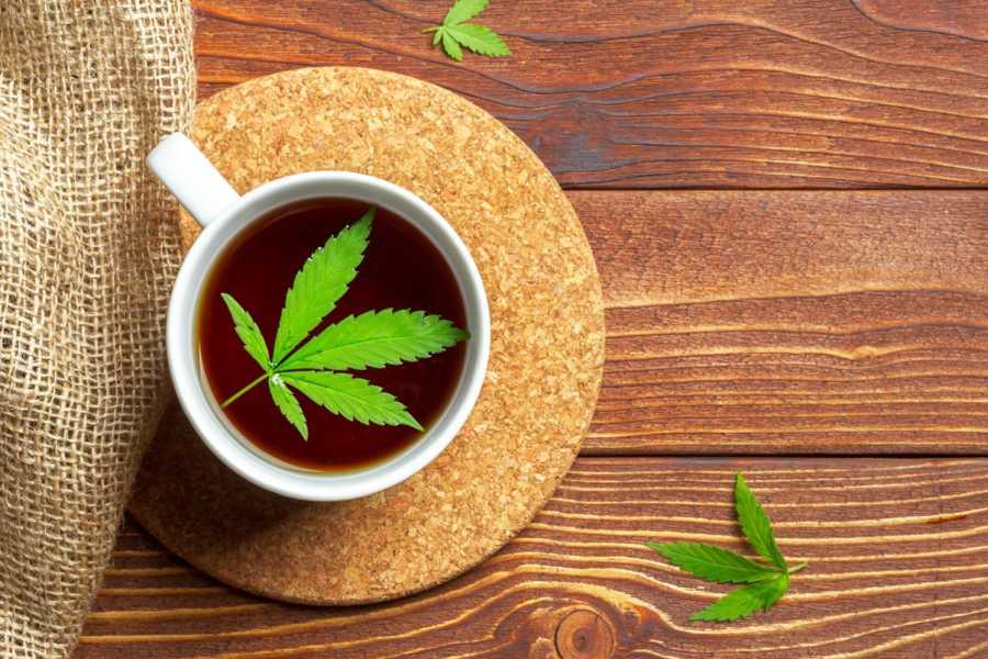 Biały kubek na drewnianym blacie i korkowej podstawce. W kubku zaparzona herbata konopna.