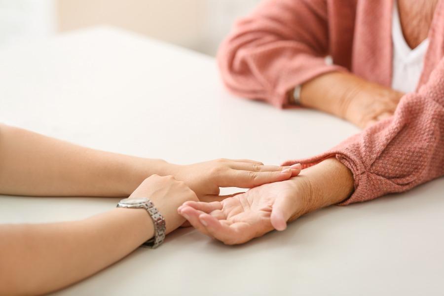 Starsza kobieta ma mierzony puls na nadgarstku. Zastanawia się, jak obniżyć puls, gdy jest wysoki.