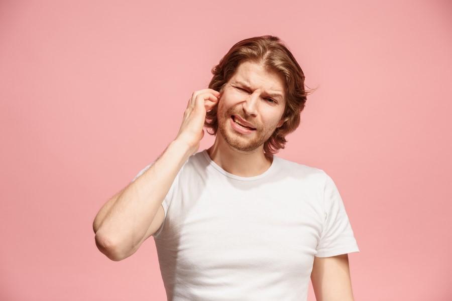 Różowe tło. Mężczyzna próbuje odetkać bolesne, zatkane ucho.