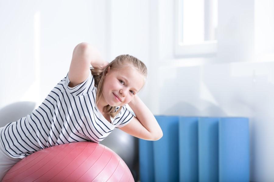 Uśmiechnięta dziewczynka na piłce gimnastycznej wykonuje ćwiczenia na kifozę.