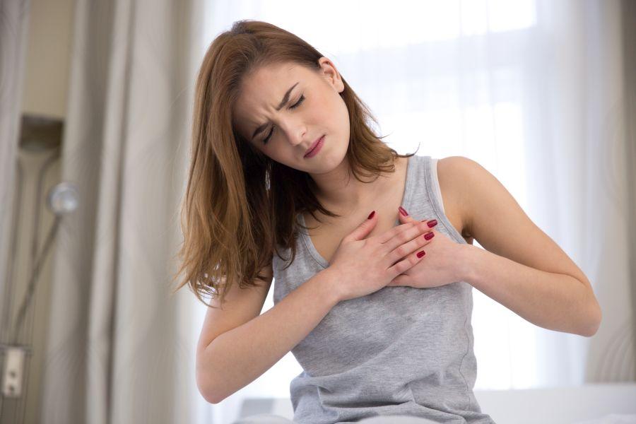 Młoda kobieta chwyta się za klatkę piersiową, odczuwa niepokojące kłucie serca