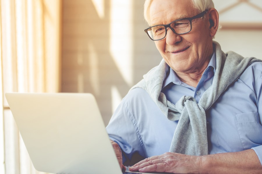 Starszy mężczyzna w okularach korzysta ze swojego laptopa.