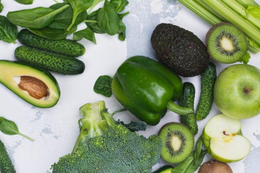 Zielone awokado, ogórki, brokuły, papryka, seler naciowy, kiwi, jabłka na białym tle.