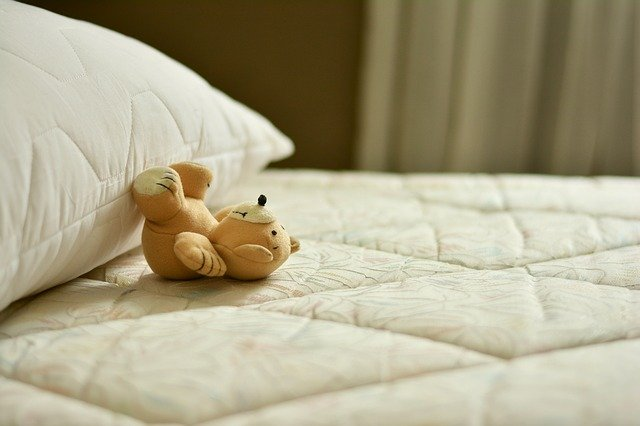 Pluszowy miś leży na materacu łóżka, oparty o poduszkę.