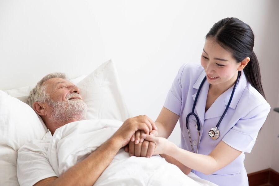Lekarka zajmuje się starszym pacjentem, leżącym w łóżku szpitalnym.