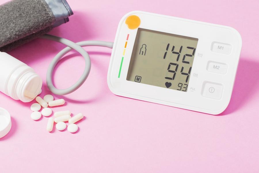 Różowe tło. Naramienny ciśnieniomierz wyświetla wyniki wskazujące na nadciśnienie tętnicze.