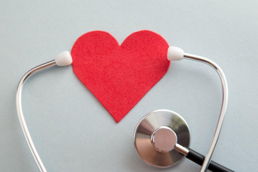 Stetoskop obejmujący słuchawkami serce wykonane z filcu.