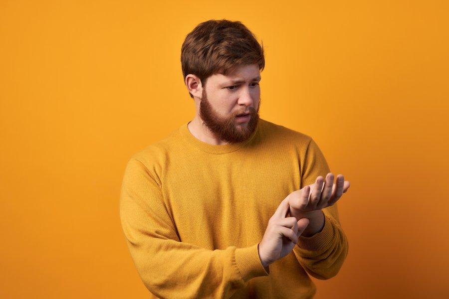 Żółte tło. Brodaty mężczyzna w żółtym swetrze mierzy sobie tętno na nadgarstku, ma niski puls.
