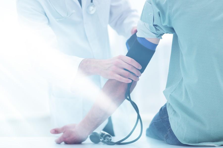 Mężczyzna ma mierzone ciśnienie u lekarza, by sprawdzić, co oznacza niskie ciśnienie i wysoki puls.