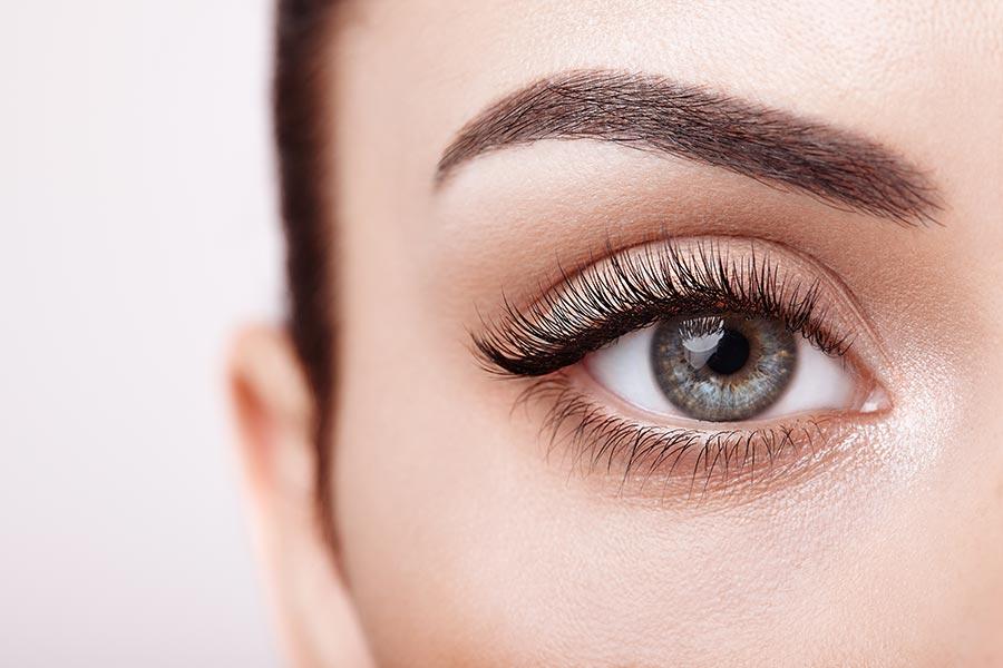 Zbliżenie na kobiece oko z pięknym wachlarzem długich rzęs.