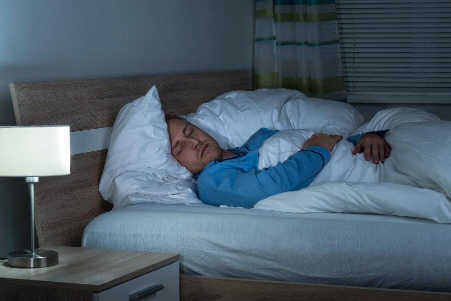 Mężczyzna w niebieskiej piżamie, śpi w swoim łóżku.