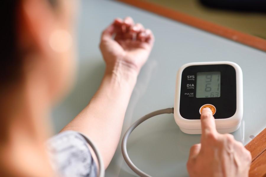 Kobieta sprawdza na elektronicznym ciśnieniomierzu naramiennym, czy ma prawidłowe ciśnienie i puls.