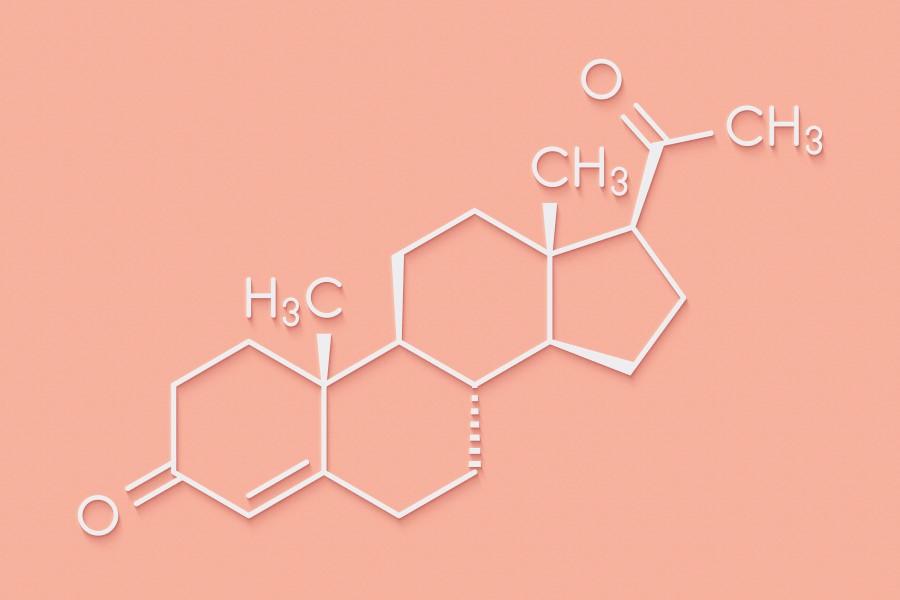 Wzór chemiczny progesteronu na różowym tle.