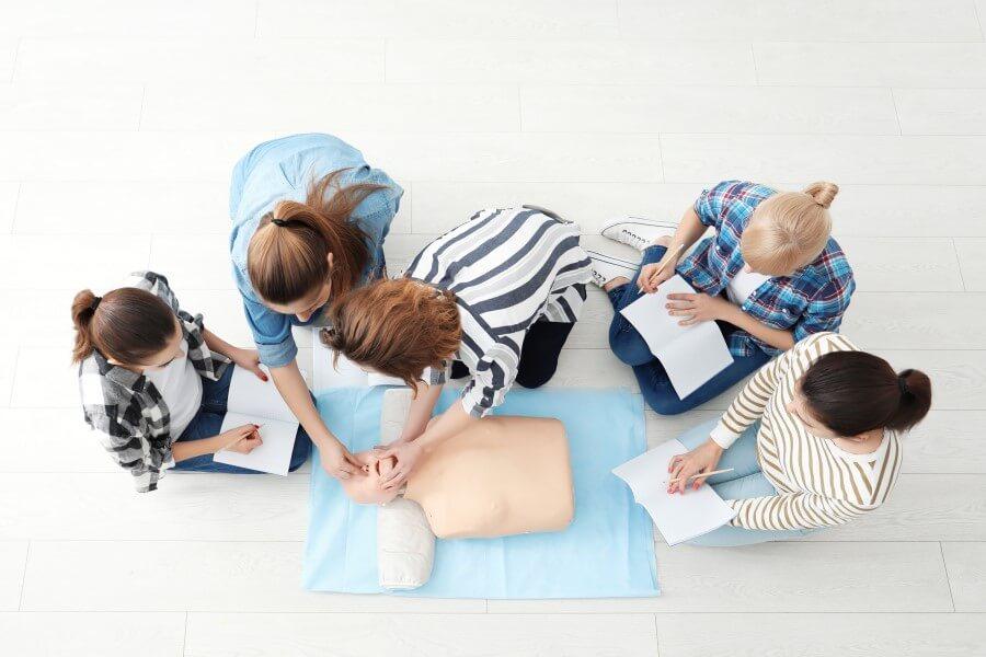 Grupa 5 osób podczas kursu resuscytacji krążeniowo-oddechowej. Robią notatki i ćwiczą na fantomie.
