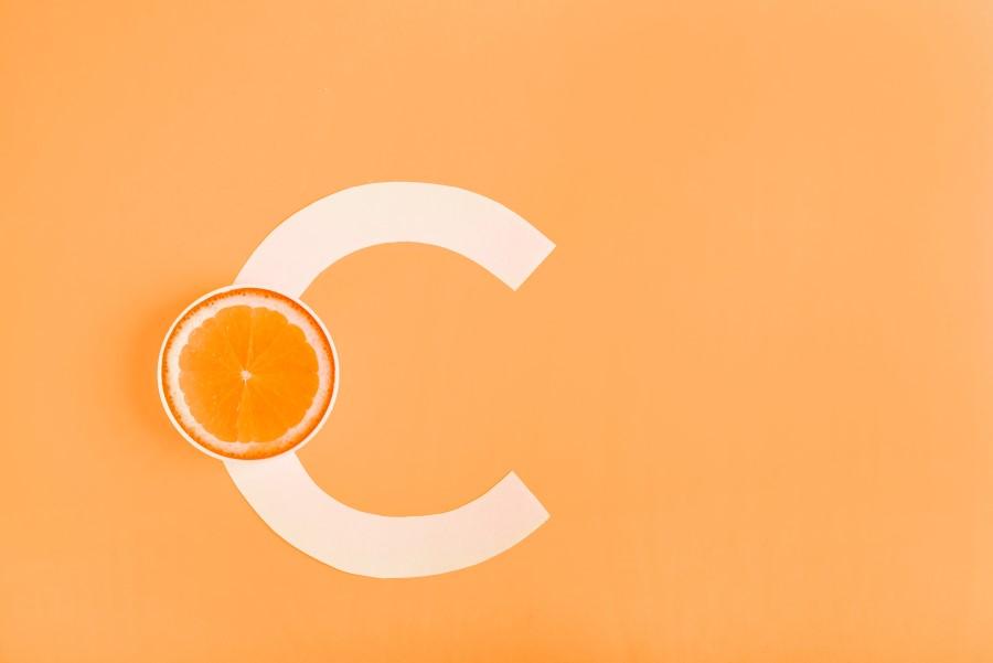 Literka C i połówka pomarańczy na pomarańczowym tle, symbolizujące witaminę C.