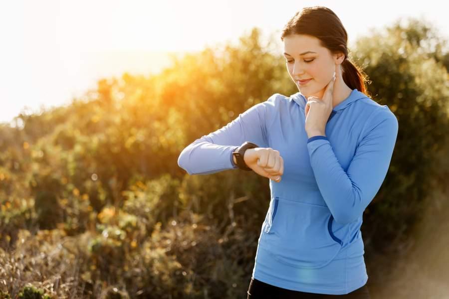 Młoda kobieta ręcznie mierzy swoje tętno maksymalne na tętnicy szyjnej, korzysta tez ze smartwatcha.