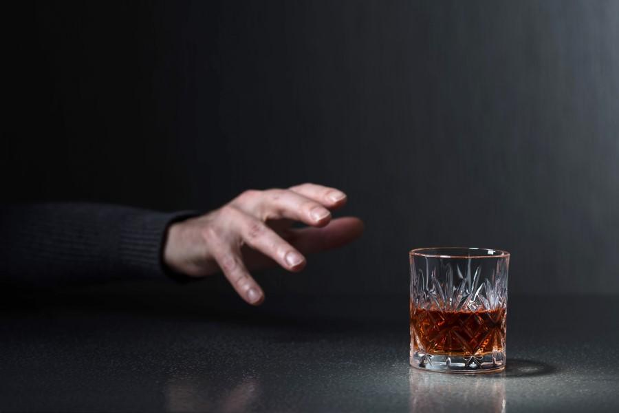 Dłoń sięgająca po szklankę z alkoholem.