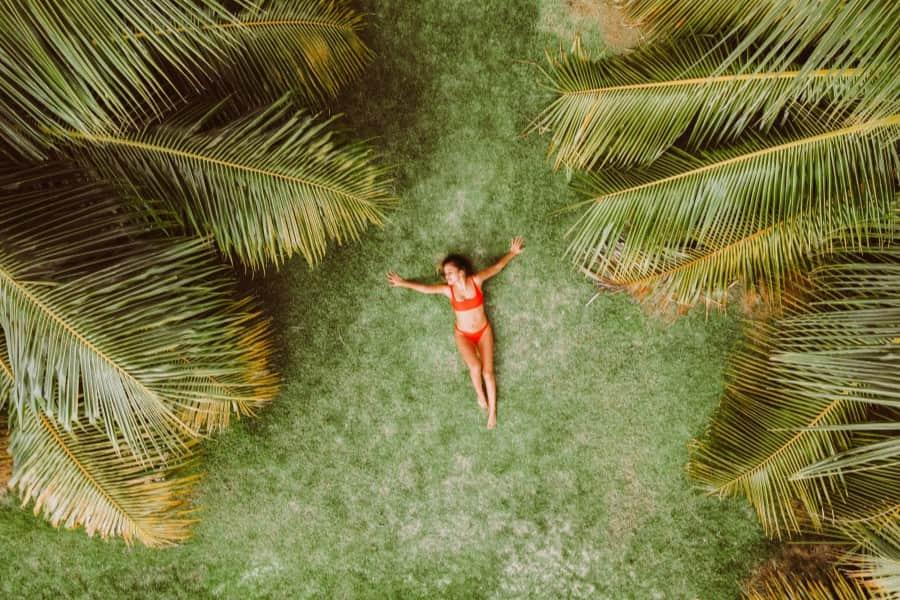 Kobieta w czerwonym stroju kąpielowym, opala się w tropikach.