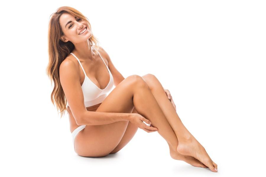 Atrakcyjna kobieta w białej bieliźnie uśmiecha się do obiektywu.