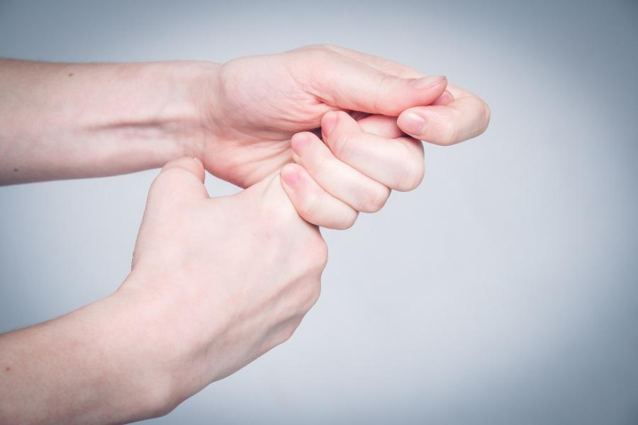Kobieta trzyma się za palec wskazujący. Na palcu rozwinął się zastrzał.