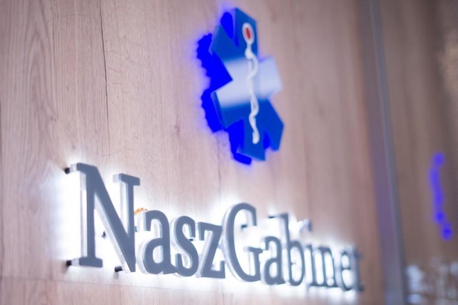 Logotyp sieci przychodni Nasz Gabinet zawieszony na ścianie.