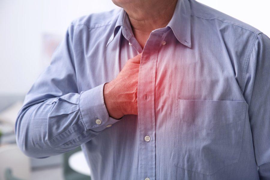 Mężczyzna chwyta się za klatę piersiową, cierpi na zespół Barlowa.